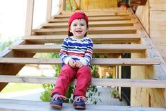 Fare da baby-sitter sorridente sulle scale all'aperto Fotografie Stock Libere da Diritti