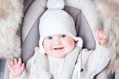 Fare da baby-sitter sorridente sveglio in un passeggiatore Immagine Stock Libera da Diritti