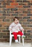 Fare da baby-sitter su un cercare della sedia Immagine Stock