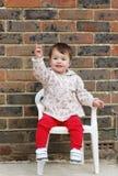 Fare da baby-sitter su una sedia che indica su Fotografie Stock Libere da Diritti