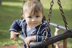 Fare da baby-sitter sulle oscillazioni Fotografia Stock