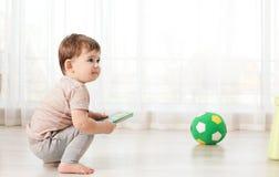 Fare da baby-sitter sveglio sul pavimento con il libro immagine stock