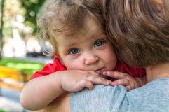 Fare da baby-sitter triste mia madre sulle sue mani Immagine Stock