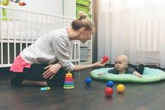 Fare da babysitter - babysitter che gioca con poco bambino sul pavimento fotografia stock libera da diritti