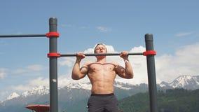 Fare dell'uomo di sport tira sull'esercizio su una barra orizzontale contro un cielo blu stock footage