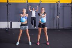 Fare della donna e dell'uomo di addestramento di forma fisica di Kettlebell tira su Immagine Stock
