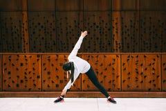 Fare della donna si china l'esercizio di forma fisica di torsione Fotografia Stock