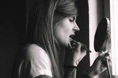Fare della donna tatuato giovani compone davanti allo specchio Immagine Stock Libera da Diritti