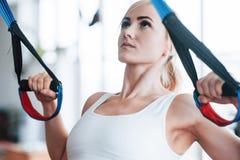 Fare delle donne spinge aumenta le armi di addestramento con le cinghie di forma fisica del trx nello sport sano di stile di vita fotografie stock