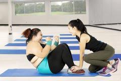 Fare grasso della donna si siede su con un istruttore Immagine Stock Libera da Diritti