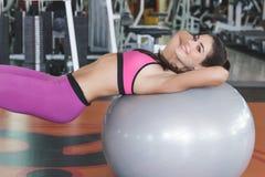 Fare grazioso della giovane donna si siede su sulla palla di esercizio Immagini Stock