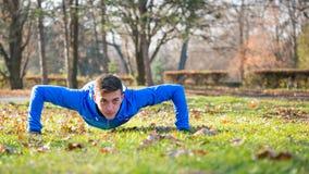 Fare maschio del corridore spinge verso l'alto sul prato inglese verde nel parco in Sunny Autumn Morning Stile di vita e concetto Fotografie Stock Libere da Diritti
