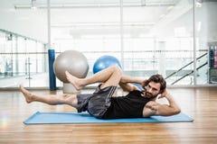 Fare muscolare dell'uomo addominale sulla stuoia Fotografie Stock