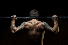 Fare muscolare maschio dell'atleta tira sull'esercizio Fotografia Stock Libera da Diritti