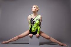 Fare professionale sveglio del gymnast spaccature sul cubo Fotografie Stock