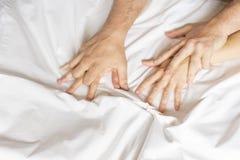 Fare sesso delle coppie La mano innesta le strette un lenzuolo sgualcito bianco in una camera di albergo, un segno di estasi, rit fotografia stock libera da diritti