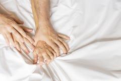 Fare sesso delle coppie La mano innesta le strette un lenzuolo sgualcito bianco in una camera di albergo, un segno di estasi, rit immagini stock libere da diritti