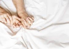 Fare sesso delle coppie La mano innesta le strette un lenzuolo sgualcito bianco in una camera di albergo, un segno di estasi, rit fotografia stock