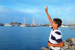 Farewell boy rising hand up goodbye. Farewell welcome boy rising hand up goodbye in marina boats summer vacation stock images
