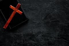 Farewell ceremony, funeral concept. Wooden cross on Bible on black background top view copy space royalty free stock photography