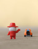 Farewell goodbye. Toy man waving hands to a departing toy car. Concept of farewell Royalty Free Stock Images