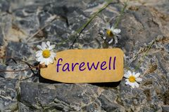 Farewell label. The farewell text written in the label with chamomile flower on the rock stock photo