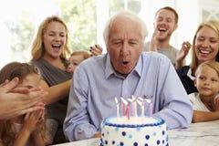 Farfadern blåser ut stearinljus för födelsedagkakan på familjpartiet Royaltyfri Fotografi