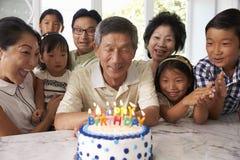 Farfadern blåser ut stearinljus på födelsedagkakan arkivfoto