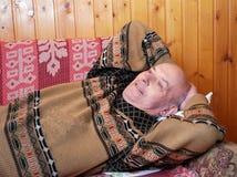 Farfadern, efter en lunch har lagt ner på en soffa för att ha att vila royaltyfria bilder