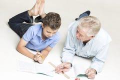 Farfadern hjälper hans sonson med läxa Arkivbild