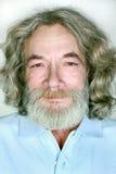 Farfadern med ett skägg och ett långt hår ler Arkivfoton