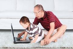 Farfadern och behandla som ett barn genom att använda bärbara datorn Fotografering för Bildbyråer