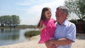 Farfadern och sondottern promenerar stranden Flickan sitter med hennes farfar på hans händer De har gyckel stock video