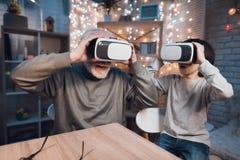 Farfadern och sonsonen använder virtuell verklighet på natten hemma royaltyfria bilder