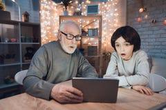 Farfadern och sonsonen håller ögonen på film på minnestavlan på natten hemma royaltyfri bild