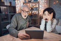 Farfadern och sonsonen håller ögonen på läskig film på bärbara datorn på natten hemma royaltyfri fotografi