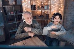 Farfadern och sonsonen lyssnar till musik i hörlurar på natten hemma fotografering för bildbyråer