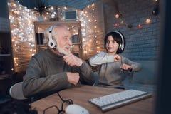 Farfadern och sonsonen lyssnar till musik i hörlurar på natten hemma royaltyfri foto