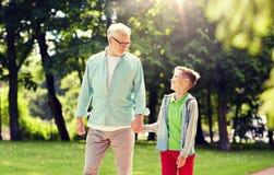 Farfadern och sonsonen som g?r p? sommar, parkerar royaltyfri foto