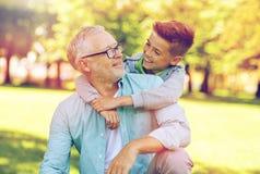 Farfadern och sonsonen som kramar på sommar, parkerar royaltyfria foton