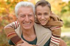 Farfadern och sonsonen som in kramar, parkerar Fotografering för Bildbyråer