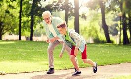 Farfadern och sonsonen som springer p? sommar, parkerar royaltyfri fotografi