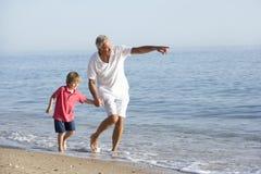 Farfadern och sonsonen som tycker om, promenerar stranden Arkivfoton
