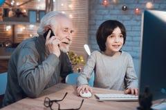 Farfadern och sonsonen spelar lekar på datoren på natten hemma Farfadern är på telefonen arkivbilder