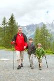 Farfadern och två pojkar som trakking på bergslinga arkivbild
