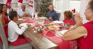 Farfadern säger nåd, som familjen sitter runt om tabellinnehavhänder på julmål arkivfilmer