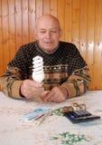 Farfadern sitter på en tabell på som att ligga räknemaskinen och pengarna, pappers- anmärkningar och mynt arkivbild
