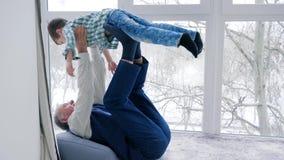 Farfadern spelas med sonsonen som inomhus ligger på golv arkivfilmer