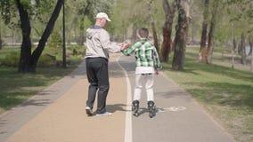 Farfadern undervisar hans sonson till rullskridskon i parkerar Fritid utomhus Farfar och sonson som spenderar tid stock video