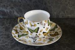 Farfalla sul teacup antico su una priorità bassa scura Fotografie Stock Libere da Diritti